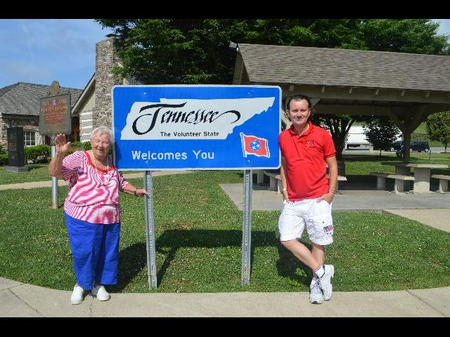 "Theresa Irene Wolowski waving hello, Ryan Janek Wolowski ""Tennessee The Volunteer State Welcomes You"" welcome sign crossing the border across the state line into Bristol, Tennessee from Virginia USA"