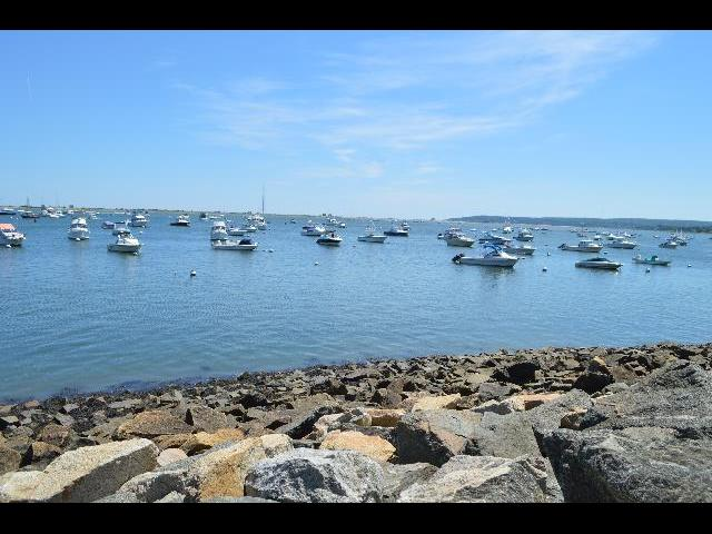 Boats docked in the harbor of Plymouth Bay where the Mayflower II 17th-century Pilgrim ship landed in Plymouth, Massachusetts, USA in 1620