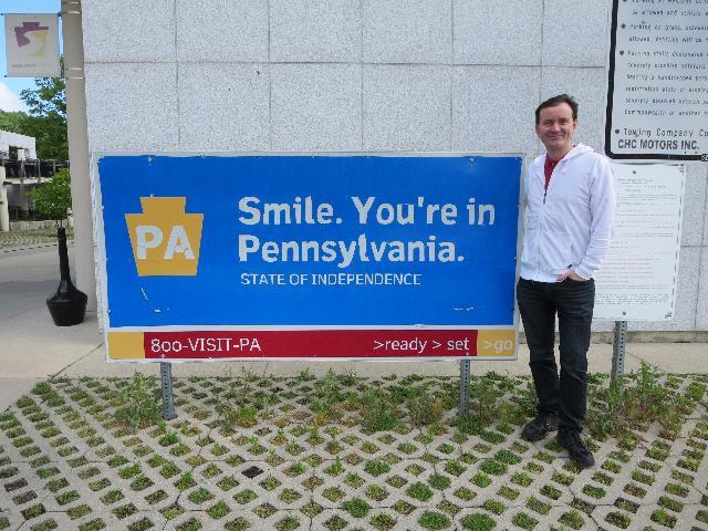 "At the ""Smile. You're In Pennsylvania"" sign at the Pennsylvania Welcome Center"
