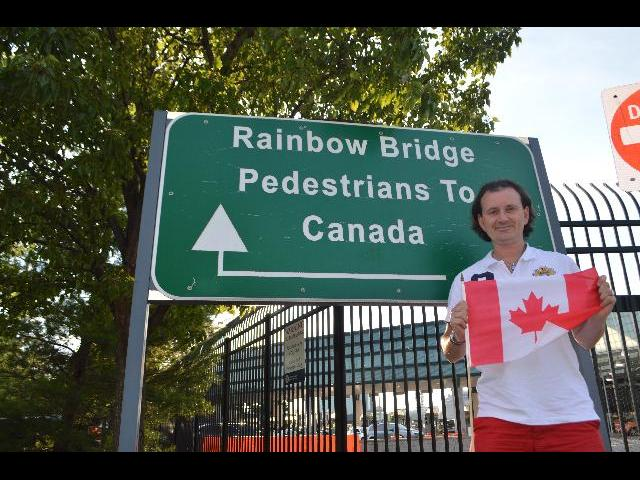 Waving The National Flag of Canada at the Rainbow Bridge Pedestrians To Canada sign at Rainbow Bridge to the Canadian Province of Ontario from New York state, United States of America