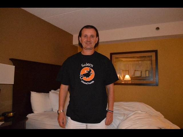Modeling a Halloween witch flying over an orange moon Salem Haunted Happenings style logo graphic theme shirt which are for sale at the Salem Witch Village est. 1692 in Salem, Massachusetts, USA