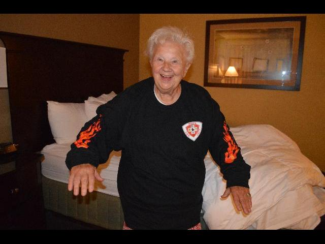 Theresa Irene Wolowski modeling a Halloween jack-o'-lantern with fire theme graphic shirt which are for sale at the Salem Ma Fire Department in Salem, Massachusetts, USA