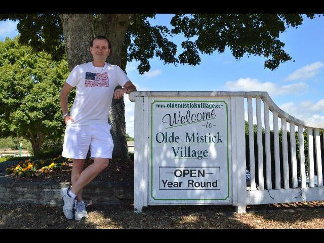 Visiting the Welcome to Olde Mistick Village sign in Mystic, Connecticut USA