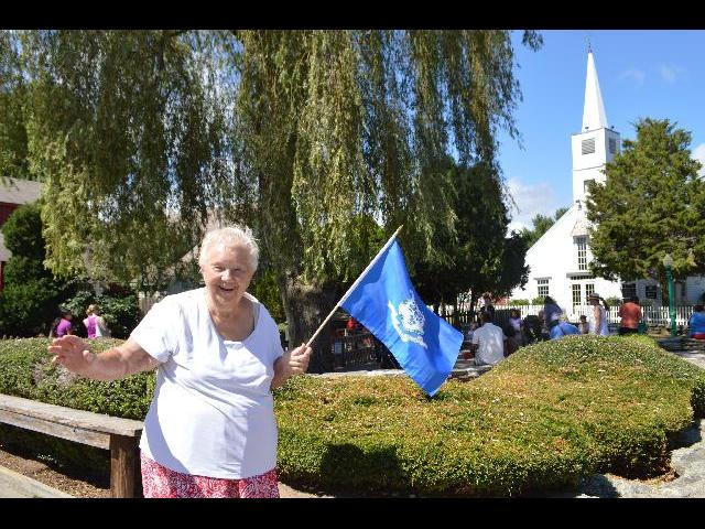 Waving hello and waving the flag of the state of Connecticut while visiitng Olde Mistick Village in Mystic, Connecticut USA