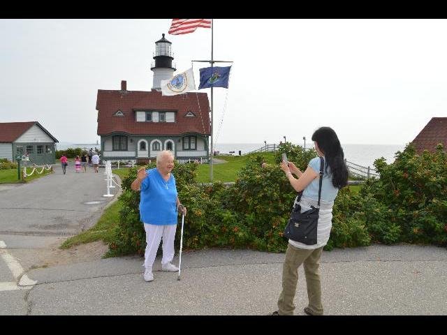 Being photographed waving hello from the Portland Head Light historic lighthouse in Cape Elizabeth, Maine, USA