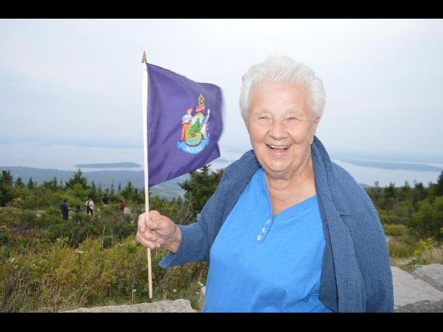 Waving the flag of the State of Maine on Cadillac Mountain, Acadia National Park, Mount Desert Island, Bar Harbor, Maine, USA