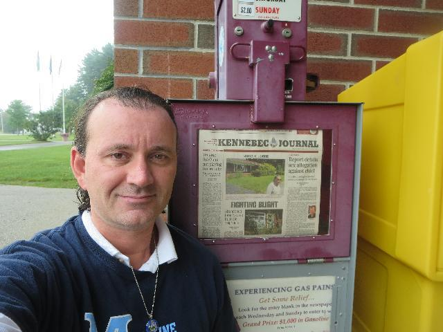 Picking up a copy of the Kennebec Journal daily newspaper in Augusta, Maine, USA