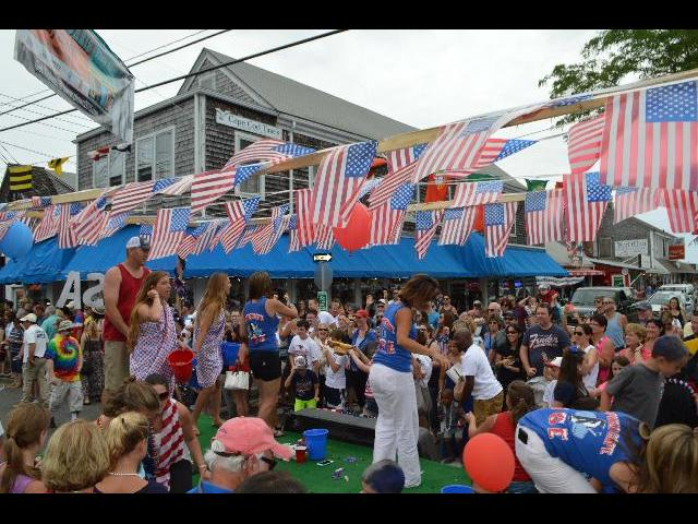 The flag of The United States of America was flying in the Fourth of July Independence Day parade on Commercial Street in Provincetown, Cape Cod, Massachusetts, New England, USA