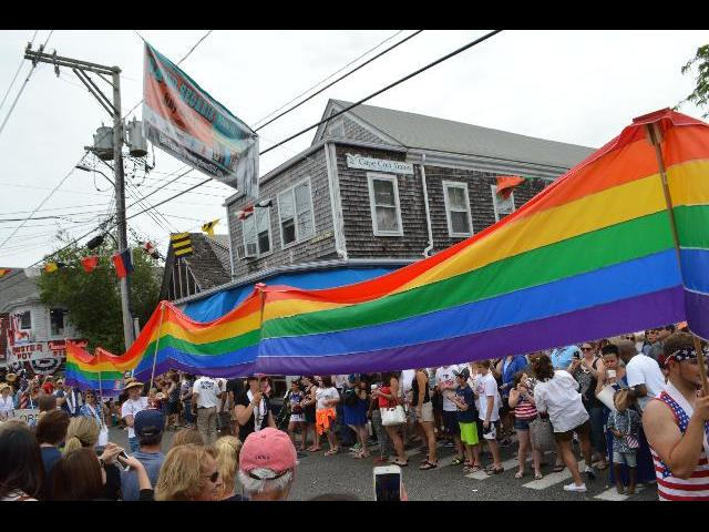 The Rainbow LGBT Lesbian Gay Bisexual Transgender Pride Flag in the Fourth of July Independence Day parade on Commercial Street in Provincetown, Cape Cod, Massachusetts, New England, USA