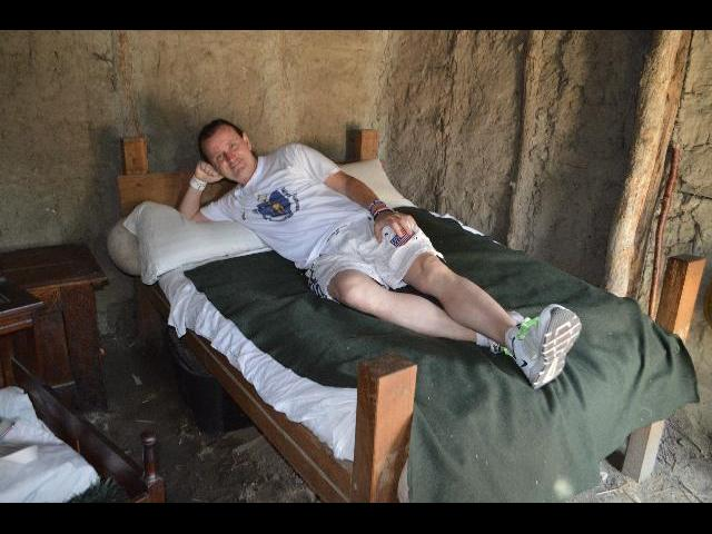 Ryan Janek Wolowski relaxing in bed of the 17th-Century English Village at the Plimoth Plantation living history museum in Plymouth, Massachusetts, New England, USA